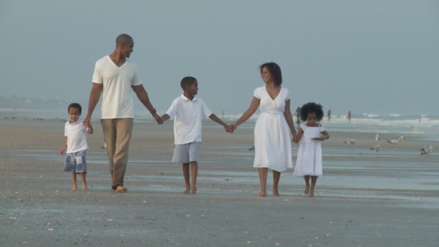 WS SLO MO Parents with children (2-9) walking on beach / Jacksonville, Florida, USA