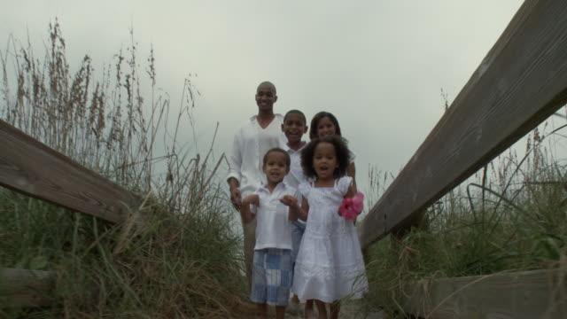 WS POV Parents with children (2-9) walking on beach walkway / Jacksonville, Florida, USA