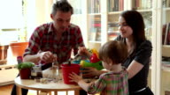 MS Parents with daughter (18-23 months) playing at art table in living room / Brooklyn, New York City, USA