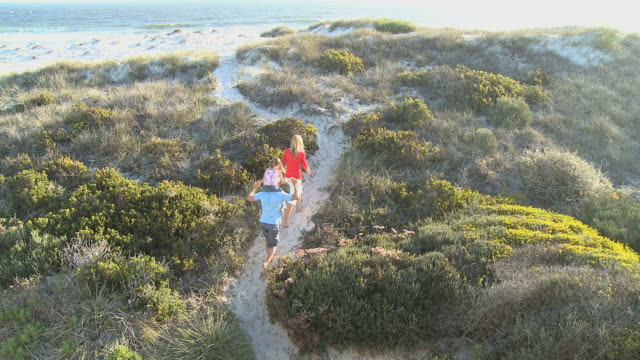 WS TU Parents with daughter (6-7) walking towards beach, father carrying daughter on shoulders / Cape Town South Africa