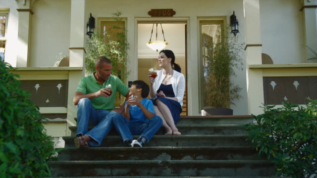 WS Parents with son (8-9) drinking iced tea on front porch of house / Seattle, Washington, USA