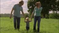 WS, CU, Parents with son (18-23 months) walking on field, Chateau du Parc, Saint Ferme, France