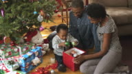 MS Parents with toddler opening gifts under Xmas Tree / Newark, New Jersey, USA