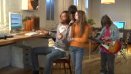 MS, Parents with two children  (8-9,10-11)  playing and singing at home