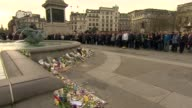 Trafalgar Square minutes silence and flowers People observing silent vigil / People looking at flowers and tributes