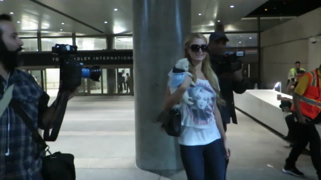 Paris Hilton and her dog enter a black SUV as she leaves Los Angeles International Airport