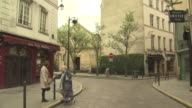 Paris St Michel Two woman talking one elderly with shopping trolley bag stand chatting on the corner of a cobbled stone street various building...