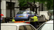 London Borough issues quotas for parking tickets Car clamped with yellow 'WCC' clamp over wheel Car being towed away as parking warden watches