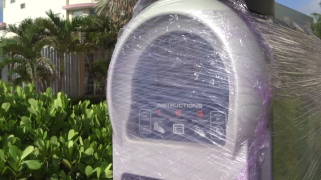 A parking meter is wrapped in plastic ahead of Hurricane Irma in Miami Florida US on Friday Sept 8 Sand bags sit by the door of a boarded up business...