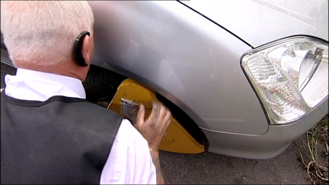 Parking officer fixing clamp to car wheel Poster for parking enforcement company Dave Durrant interview SOT View through side mirror Clamps in back...