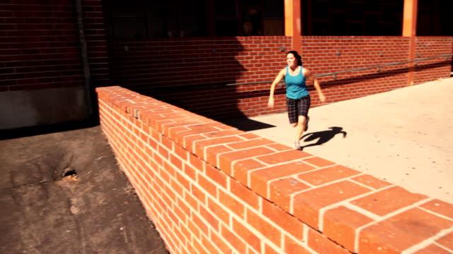 Parkour- Mädchen nutzt verschiedene Gewölbe die Hindernisse zu überwinden