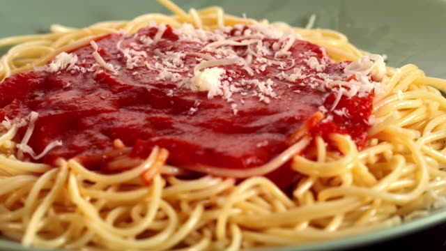 MS DS Parmesan cheese being sprinkled over rotating spaghetti dish topped with tomato sauce for pasta marinara / Los Angeles, California, United States