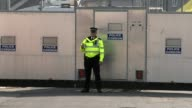 More details emerge about suspects ENGLAND Surrey SunburyonThames EXT Police officer standing in front of large steel police cordon at Cavendish Road...