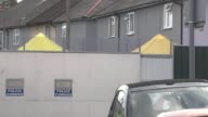 More details emerge about suspects Surrey SunburyonThames EXT Blue and yellow tent outside raided house and police officer along **Griffiths...