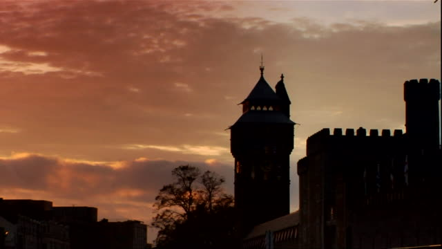 Partial Cardiff Castle tower clouds passing BG turning dark tower becoming silhouette UK