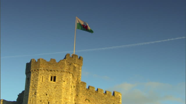 Partial Norman Keep w/ Flag of Wales on pole on top of tower streak some clouds in mostly clear blue sky BG Medieval Victorian United Kingdom UK