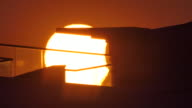 Partial solar eclipse at sunset with modern building framing shot