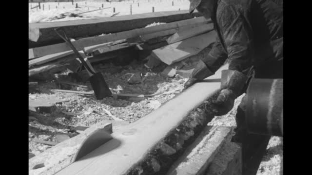 Partially built wooden boat on snowy beach / three shots of ship builders sawing planks for boat / two shots of men using planes to smooth plank /...