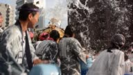 Participants carrying a portable shrine to the Fukagawa hachimangu Shrine are showered with water from buckets during a festival in Tokyo Japan on...