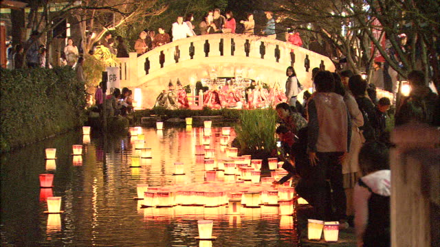 Participants release floating paper lanterns onto the river in Saga City, Japan.