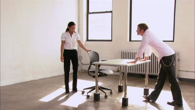 Partners in startup firm looking at new desk and chair in empty loft space / New York City
