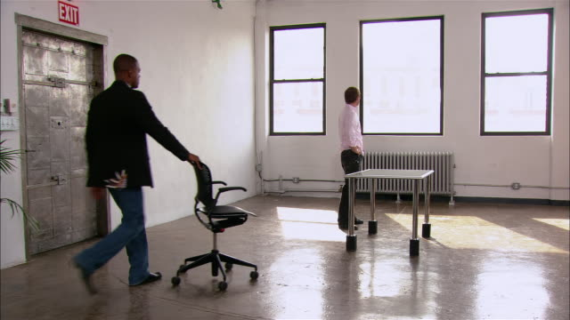 Partners in startup firm moving first desk and chair into empty loft space / New York City