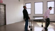Partners in startup firm moving first desk into empty loft space / New York City