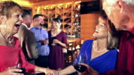 Party in restaurant, waitress serving wine
