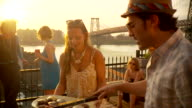 MS PAN Party scene, man preparing barbecue, woman carrying food / Brooklyn, New York