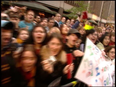DAY WALKING pass fans mostly teenage girls behind barricade on street across from Ziegfeld Theatre screaming waving holding up homemade signs PAN to...
