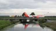 A passenger aircraft operated by EasyJet Plc crosses a bridge after landing at Schiphol airport in Amsterdam Netherlands on Tuesday Aug 15 2017
