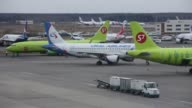 Passenger aircraft operated by S7 Airlines stand before flight at Domodedovo Airport ZAO in Domodedovo Russia on Friday April 21 Employees prepare an...