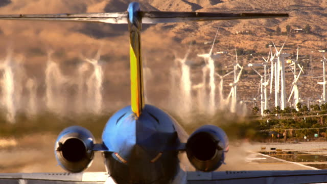 WS SLO MO passenger jet enters runway and accelerates for takeoff spewing thick clouds of hot jet exhaust fumes and gases being pumped out of jet engines /Palm Springs, California, USA