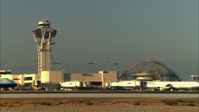 MS, Passenger jets on tarmac with air traffic control tower in background, sunset, Los Angeles, California, USA