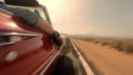 A passenger rests his arm on the door of a red convertible driving down a desert highway.