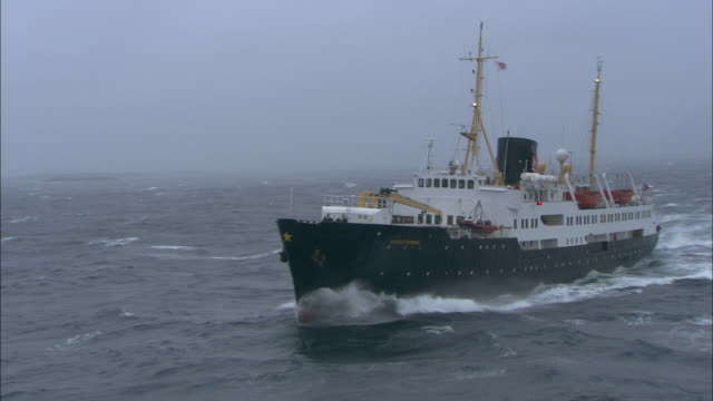A passenger ship sails through rough seas off the coast of northern Norway.