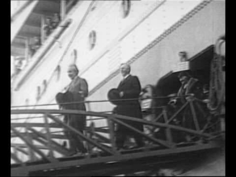Passenger steamship sails in ocean / physicist Albert Einstein with wife Elsa on board ship / Einstein walks down gangplank / LS row of schoolgirls...