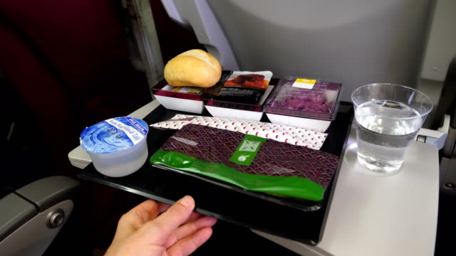A passenger takes his lunch in a Qatar Airways plane 4K resolution