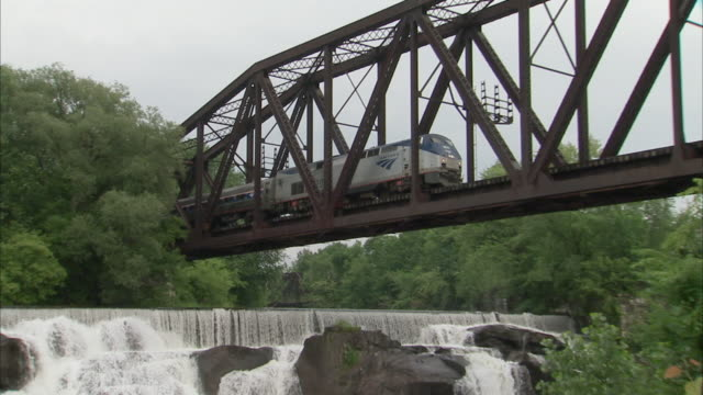 CU ZO WS Passenger train crossing bridge over river with small waterfalls / Rutland, Vermont, USA