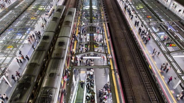 TL, HA, WS Passengers board and disembark from trains at rush hour in Osaka station / Osaka, Japan