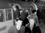 Passengers disembark and embark onto a crowded tube train