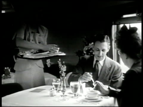 Passengers in dining car waitress waiter MS Middle aged couple at table waitress serving soup MS Waitress MS Mother w/ baby receiving tray from...