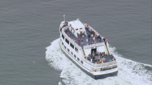 AERIAL Passengers on board the deck of ferry cruising through the water / Boston, Massachusetts, United States