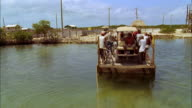 Passengers ride water taxi across small river, Belize Available in HD.