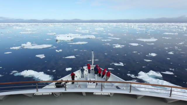 Passengers scurry across a ship's bow as they travel through ice floes near the Arctic Circle.