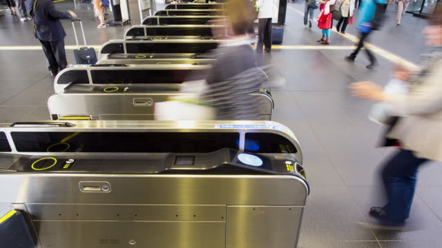 Passengers walk through a ticket barrier in a train station, Japan