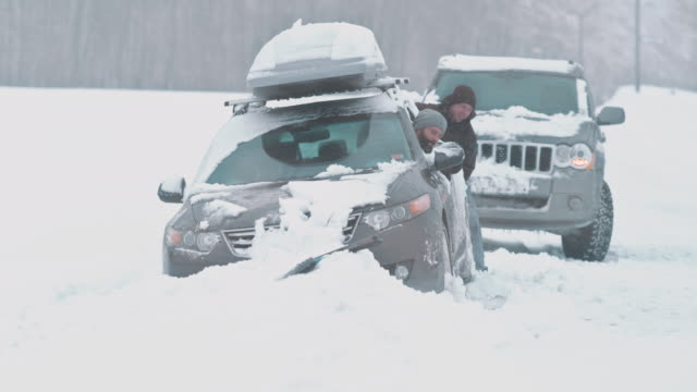 LD Passing driver assisting by pushing a stucked car out of snow