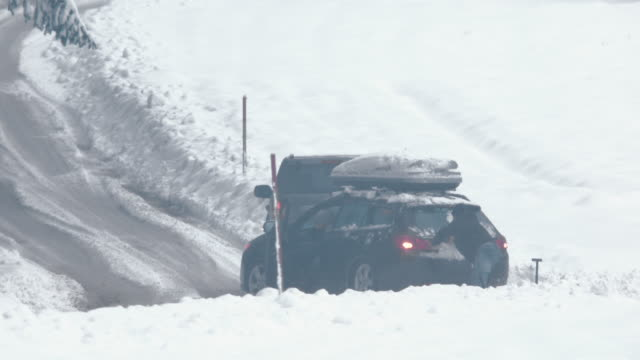 Passing driver helps pushing a car out of snow