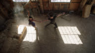 SLO MO. Passionate ballroom dancers twirl as sunlight catches the dust in mysterious rustic setting.
