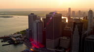 MEDIUM AERIAL SIDE POV past buildings in Lower Manhattan and New York Harbor at sunset